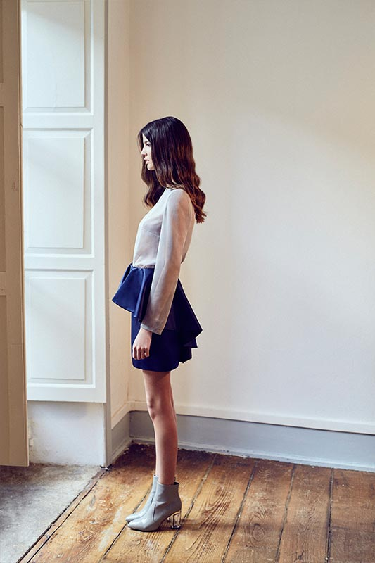 Modelo mirando por la ventana con falda mini con volante
