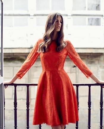 Modelo en balcón con vestido midi de encaje